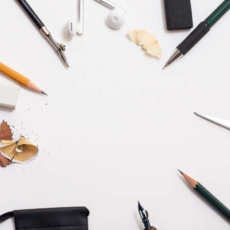 Background with white paper, pencils and eraser. Workplace for the painter. Background to display the logo and lettering. copyspace, space for text. the blogger instrument. Banco de Imagens