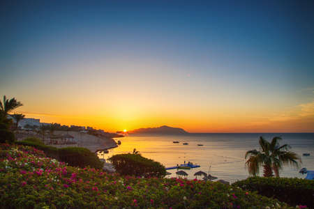 Sunrise over the red sea. Beautiful bright sky with sun rays and morning clouds. Sea and boats. View of Tiran Island. Egypt, Sharm El Sheikh. Tourism and travel. Rest and vacation.