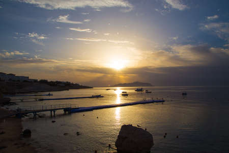 Sunrise over the red sea. Beautiful bright sky with sun rays and morning clouds. Sea and boats. View of Tiran Island. Egypt, Sharm El Sheikh. Tourism and travel. Rest and vacation. Stock Photo