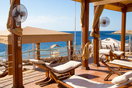 white chaise against the sea. beautiful seashore, holiday and relax.