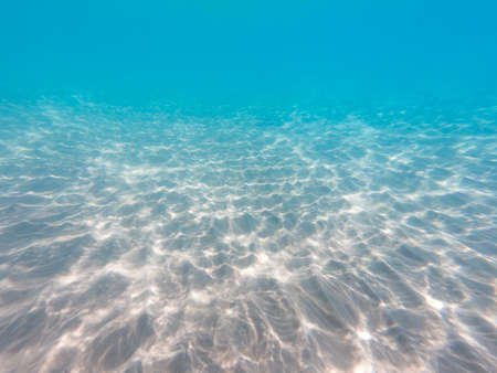 underwater background with sandy sea bottom. Beautiful texture of the sea and ocean water. Imagens