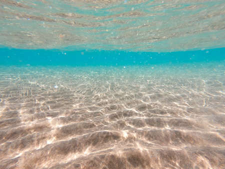 underwater background with sandy sea bottom. Beautiful texture of the sea and ocean water.