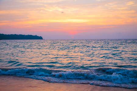 puesta de sol sobre el mar. playa de arena, agua clara, olas. Foto de archivo