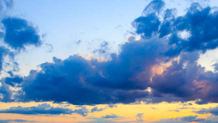 Bright cumulus clouds against the blue sky. Sunset sky Natural background.