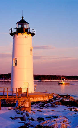 Portsmouth lighthouse guides lobster boat home during winter season   Stock Photo