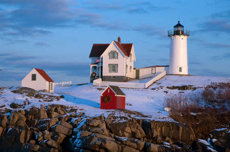 Snow covered lighthouse during holiday season in Maine.