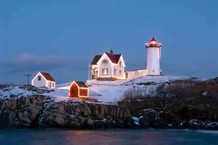 Southern Maines Nubble lighthouse lit at dusk during the holidays.