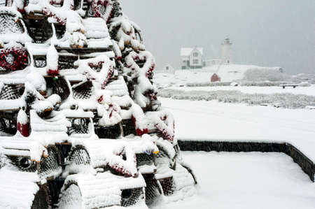 guiding light: Snow covered holiday lobster trap tree near lighthouse.