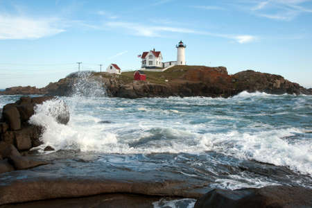 surrounds: High tide surrounds the nubble island of Cape Neddick lighthouse in southern Maine.