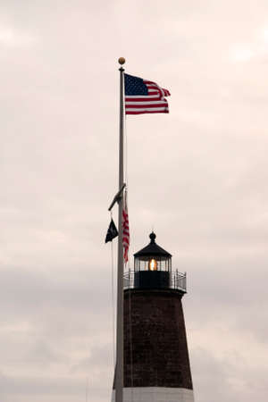 guiding light: American flag waves over Point Judith lighthouse in Rhode Island.