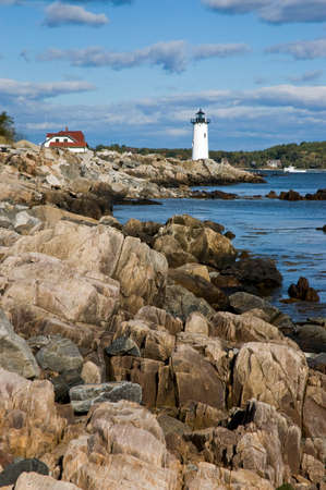 guides: Portsmouth Lighthouse guides mariners away from the rocky shoreline. Stock Photo