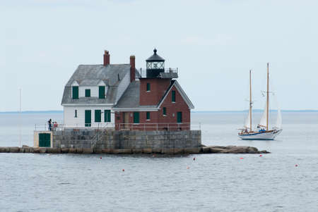 high tide: Sailboat passes by Rockland Breakwater lighthouse in mid coast Maine during high tide.