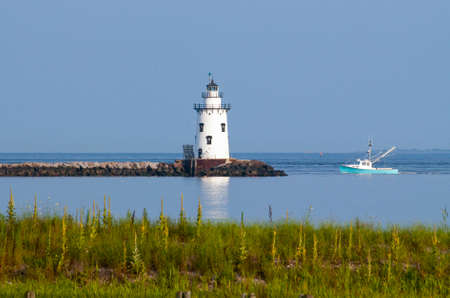 Saybrook Breakwater lighthouse guides fishing boat home in Connecticut.