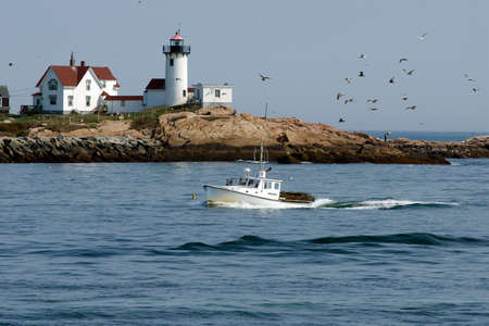 lobster boat: Lobster boat returning home guided by Eastern Point Lighthouse.