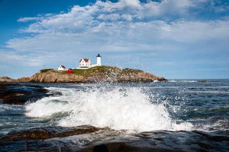 waves crashing: Waves crashing on rocks by lighthouse in Maine.
