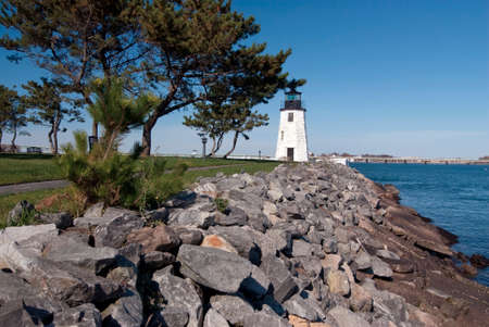 breaker: Newport harbor lighthouse is protected by a breaker from New England storms.