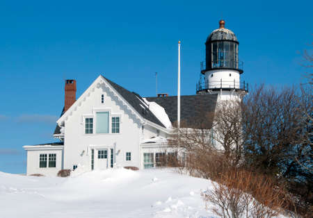 icey: Cape Elizabeth lighthouse in Maine is buried in snow after a winter snowstorm passed the day before. The beacon is still one of the most powerful lights on the Maine coast. Stock Photo