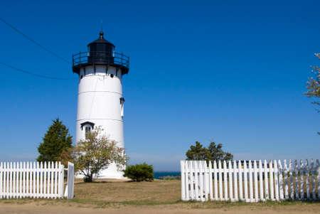 guiding light: Picket fence by lighthouse on Marthas Vineyard in Massachusetts. Stock Photo