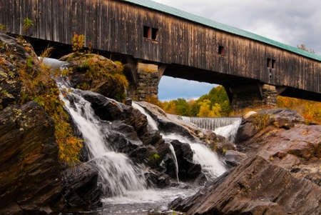 covered bridge: Old wooden covered bridge over cascading waterfalls on an autumn day in Bath, New Hampshire.