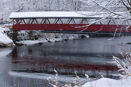 icey: Snowing on covered bridge in New England.