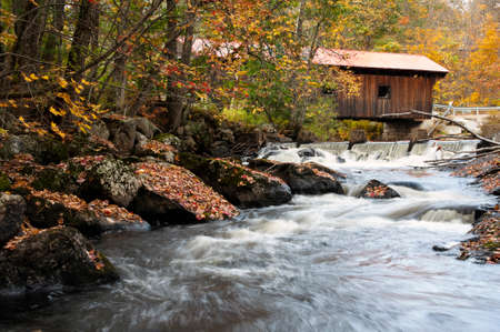 rushing water: Waner covered bridge over rushing water on an autumn day in New England. Stock Photo