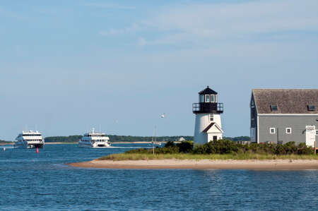 ferries: Two ferries pass by Hyannis Harbor lighthouse on a summer day in Cape Cod, Massachusetts.