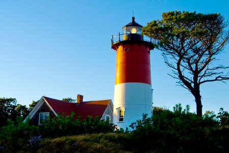 guiding light: Nauset Lighthouse lantern shines brightly at dusk on a summer evening on Cape Cod, Massachusetts.