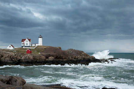 Storm clouds over Nubble lighthouse as waves crash on rocky coast of Maine.