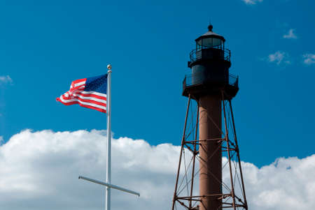 American flag waves by Marblehead lighthouse in Massachusetts.