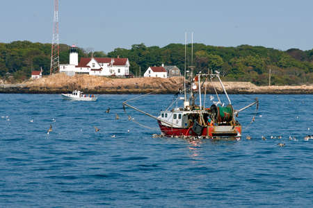 Fishing trawler by lighthouse, coming home in Gloucester, Massachusetts.