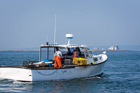 Lobstermen haul traps on a summer day in Maine with lighthouse in the distance.