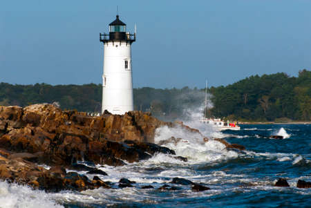 Portsmouth Harbor lighthouse guides fishing boat through dangerous surf. Stock Photo
