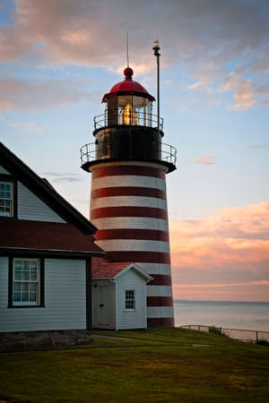 Authentic fresnel lens of West Quoddy head lighthouse, famous for its red and white srtipes, shines brightly during sunset in northern New England. It is the easternmost beacon in America. Stok Fotoğraf