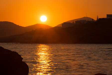 beautiful orange seascape with calm water sunset above mountains with calm water