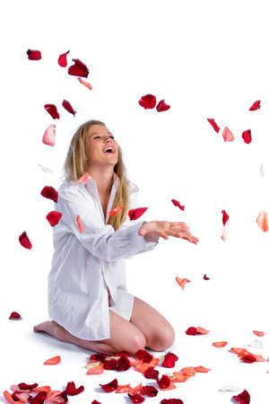 portrait of woman in white shirt throwing up rose-petals photo