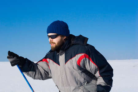 portrait of handsome skier in the snowy field
