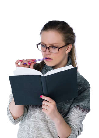 intent looking girl in glasses write in book. white background