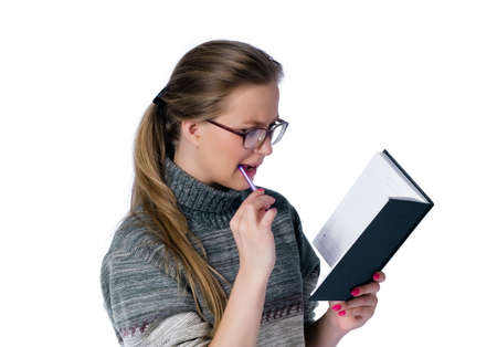 intent: intent looking girl in glasses write in book. white background