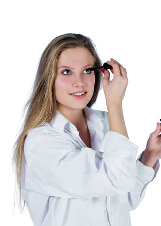 portrait of young woman applying mascara photo