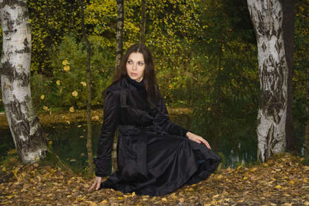 waterproof cape: woman siting on bank in autumn park