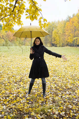 waterproof cape: pretty laughing woman with yellow umbrella in autumn park