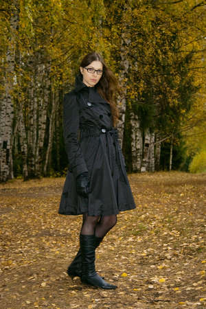 strict pretty woman in glasses standing in autumn park photo