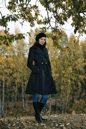 waterproof cape: pretty woman in black beret in autumn park