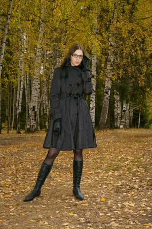 strict pretty woman in glasses standing in autumn park Stock Photo