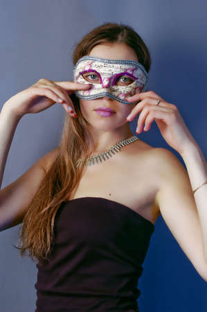 young woman in carnival mask on blue background