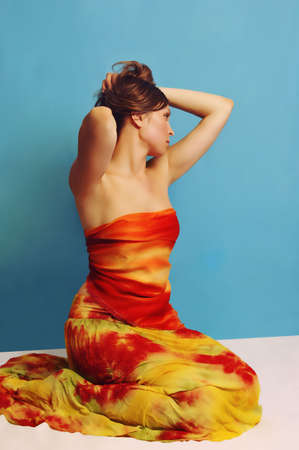 young woman in sarong on blue background