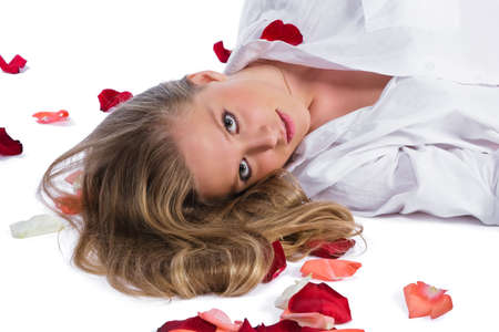 uncombed: woman in white shirt lying among rose-petals