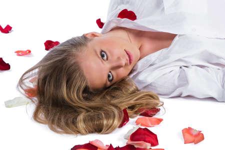woman in white shirt lying among rose-petals