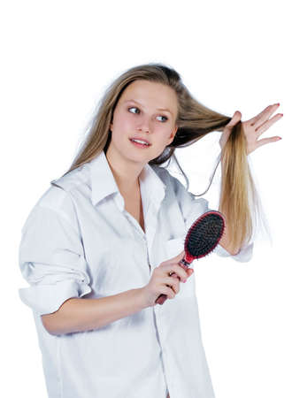 portrait of young woman in white shirt combing ones hair. white background Stock Photo