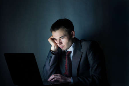 late: businessman working with computer at night